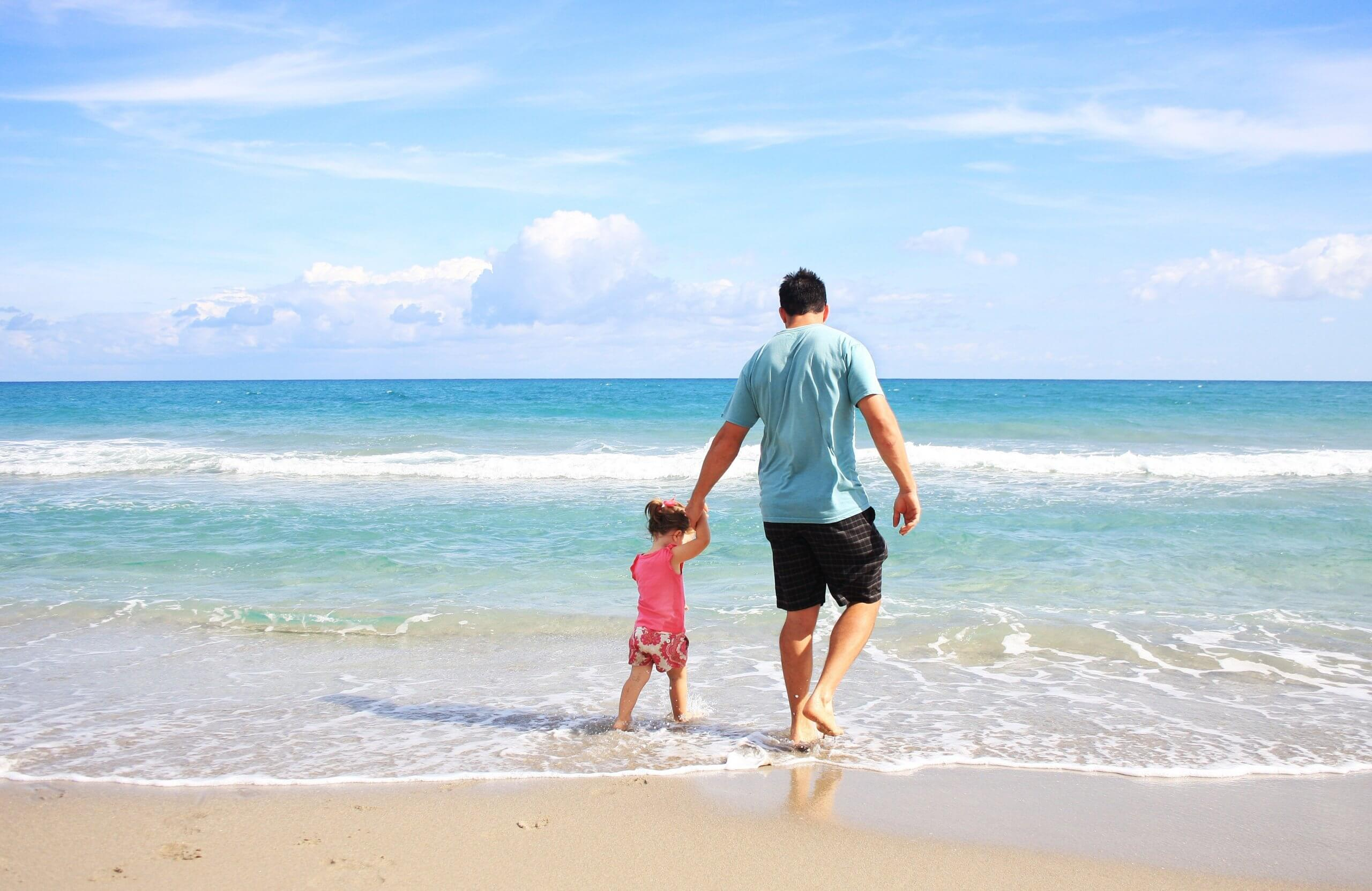 Child with parent on beach during summer visitation